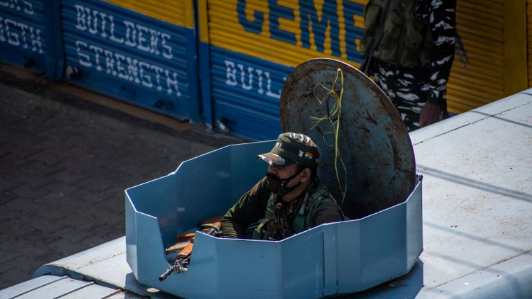 SRINAGAR, KASHMIR - INDIA - AUGUST 05: An Indian paramilitary trooper guards atop his armored vehicle in a deserted city square,  during a curfew like restrictions, a year after India revoked the special status of Jammu and Kashmir, on August 05, 2020  in Srinagar, the summer capital of Indian administered Kashmir, India. Indian police and paramilitary personnel were deployed in strength as authorities imposed curfew-like restrictions in summer capital city Srinagar  on the first anniversary of the Indian government stripping the Himalayan region, contested by both India and Pakistan since 1947, of its autonomy and downgrading its status from a state to a union  territory in a stealth move last year. The region is already reeling under a lockdown imposed by authorities to curb the spread of coronavirus. (Photo by Yawar Nazir/Getty Images)