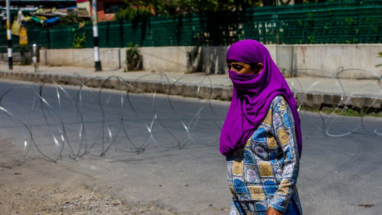 SRINAGAR, KASHMIR - INDIA - AUGUST 05: A Kashmiri Muslim woman walks in front of a concertina razor wire of Indian government forces closing a road in the deserted city center during a curfew like restrictions, a year after India revoked the special status of Jammu and Kashmir, in the city center  on August 05, 2020  in Srinagar, the summer capital of Indian administered Kashmir, India. Indian police and paramilitary personnel were deployed in strength as authorities imposed curfew-like restrictions in summer capital city Srinagar  on the first anniversary of the Indian government stripping the Himalayan region, contested by both India and Pakistan since 1947, of its autonomy and downgrading its status from a state to a union  territory in a stealth move last year. The region is already reeling under a lockdown imposed by authorities to curb the spread of coronavirus. (Photo by Yawar Nazir/Getty Images)