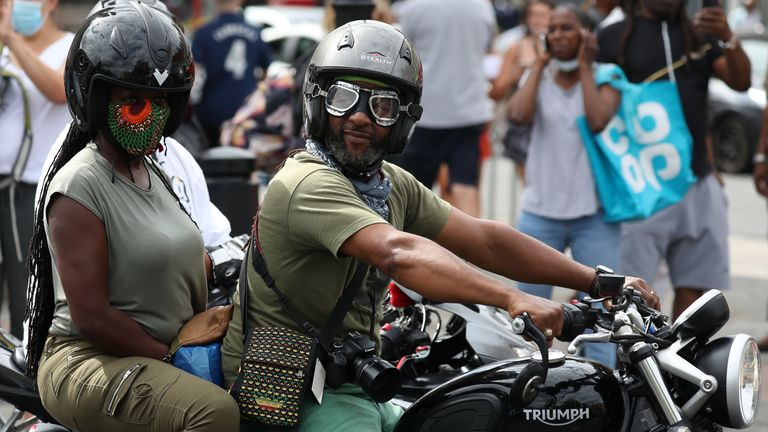 A motorcyclist is seen looking on at the celebrations during the event in Brixton