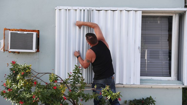 A man boards up his window in Florida ahead of the storm's arrival