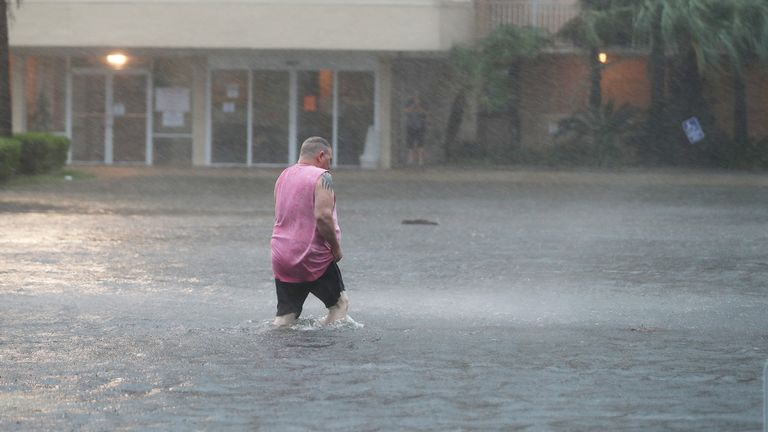 Hurricane Sally Makes Landfall On Gulf Coast GULF SHORES, ALABAMA - SEPTEMBER 15: A man walks though a flooded parking lot as the outer bands of Hurricane Sally come ashore on September 15, 2020 in Gulf Shores, Alabama. The storm is bringing heavy rain, high winds and a dangerous storm surge from Louisiana to Florida. (Photo by Joe Raedle/Getty Images)