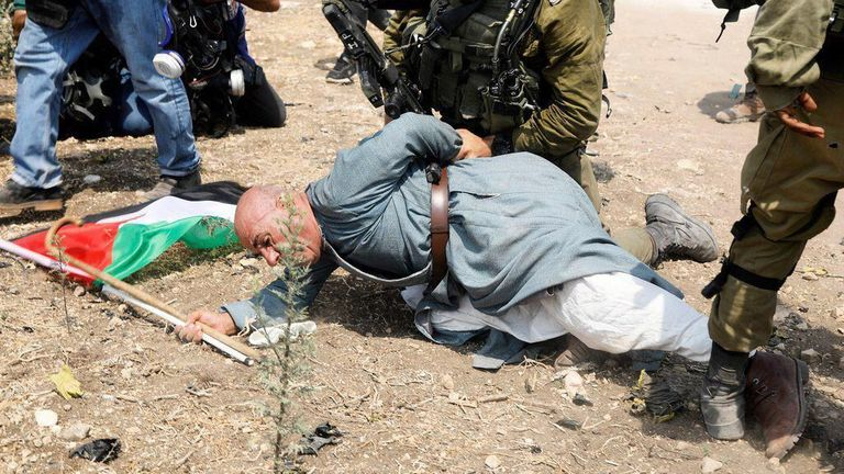 Khairi Hannoun being restrained by an Israeli soldier