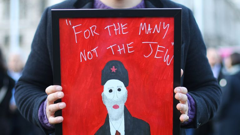 "A demonstrator holding a painting saying ""For the many not the Jew"", as people protest against anti-Semitism in the Labour party in Parliament Square, London, as Jewish community leaders have launched a scathing attack on Jeremy Corbyn, claiming he has sided with anti-Semites ""again and again""."