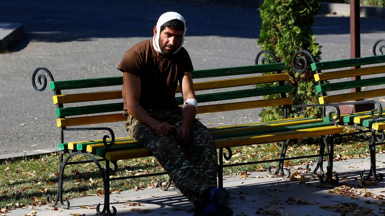 An injured man sits on a bench near a hospital in Stepanakert in the breakaway region of Nagorno-Karabakh