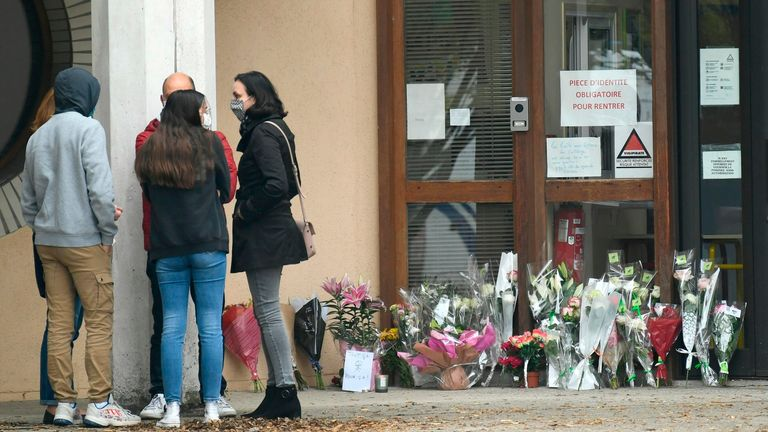 Flowers have been placed at the entrance of a middle school in Conflans-Sainte-Honorine, 30kms northwest of Paris, on October 17, 2020, after a teacher was decapitated by an attacker who has been shot dead by policemen