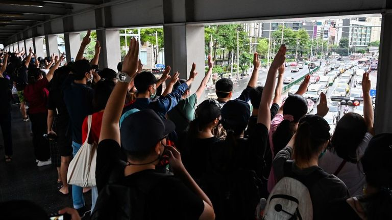 The three-finger salute shown to motorists during a flash mob at Asok BTS skytrain station in Bangkok