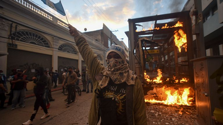 A bus stop burns as people protested in Guatemala City on Saturday