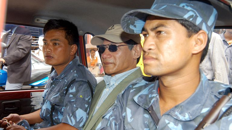 """French national Charles Sobhraj (C) takes a taxi back to jail while accompanied by guards in the Nepalese capital Kathmandu July 5, 2004. Nepali authorities on Monday charged the notorious criminal Sobhraj, known as """"the Serpent"""" and the """"Bikini Killer"""", with the 1975 murder of an American backpacker in Kathmandu. REUTERS/Gopal Chitrakar GC/TW"""