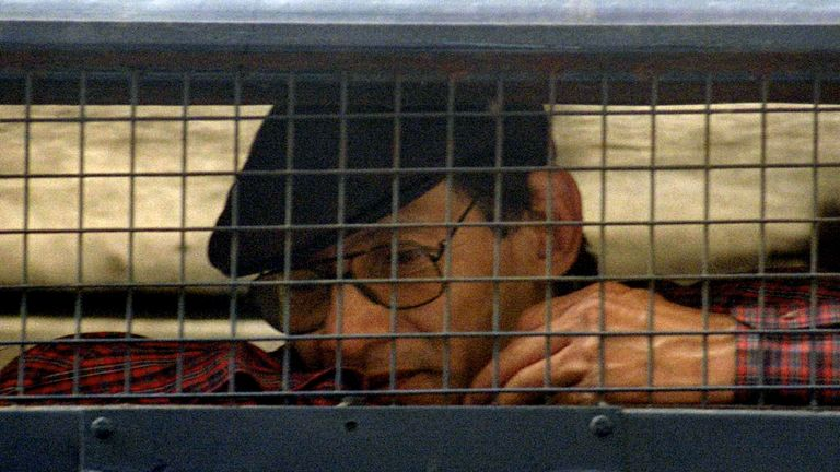 Renowned criminal Charles Sobhraj, 52, sits inside a police van outside a New Delhi court February 24. India formally ordered that Sobhraj, who has faced charges of murder, robbery and jailbreak, to be deported to his native France and barred his re-entry into India.